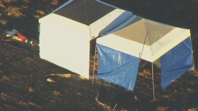 An investigative tent stands where a helicopter crashed